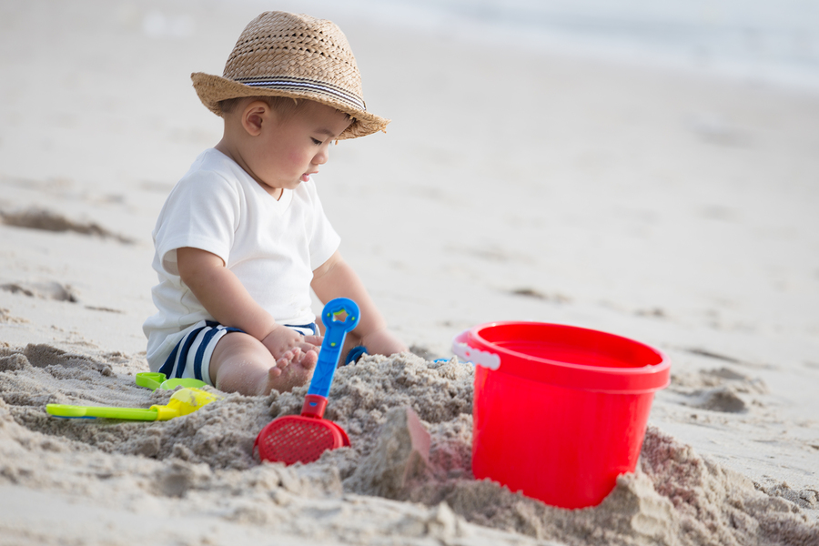 Baby boy playing in the sand on the beach